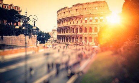 Sun over Colosseum in Rome, Italy
