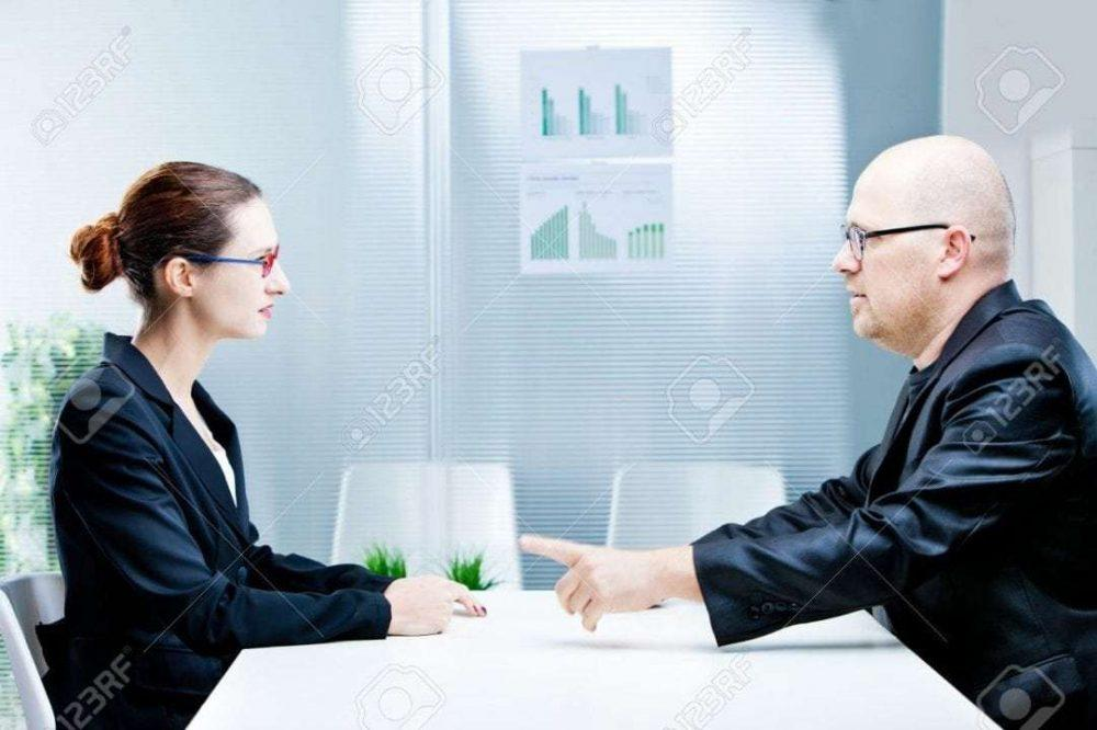 business man and business woman discussing facing each other in a polite discussion