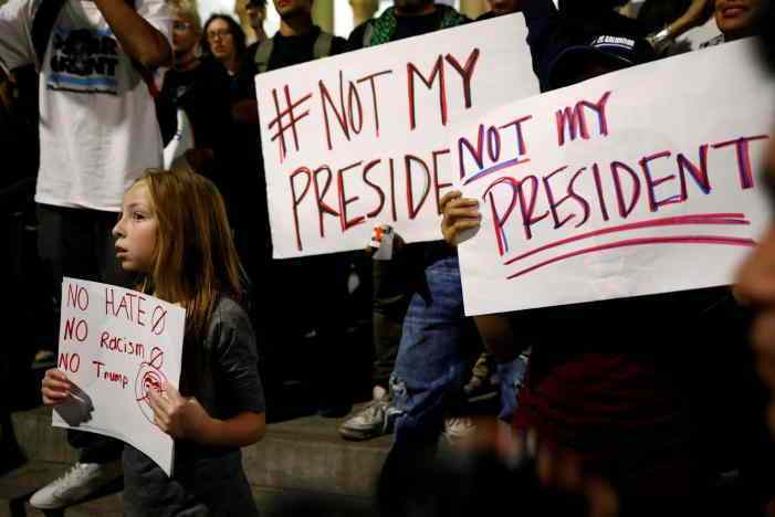 A girl joins demonstrators to protest outside of City Hall following the election of Republican Donald Trump as President of the United States in downtown Los Angeles, California November 10, 2016. REUTERS/Patrick T. Fallon