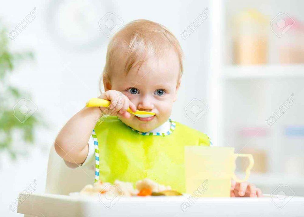 37330758-happy-baby-child-sitting-in-chair-with-a-spoon-stock-photo-baby-food-eating