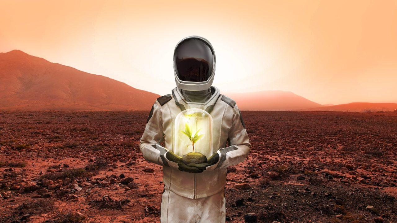 Φυτά στον Άρη: Αστροναύτης στον Άρη κρατάει ένα φυτό μέσα σε γυάλα Αστροναύτης στον Άρη