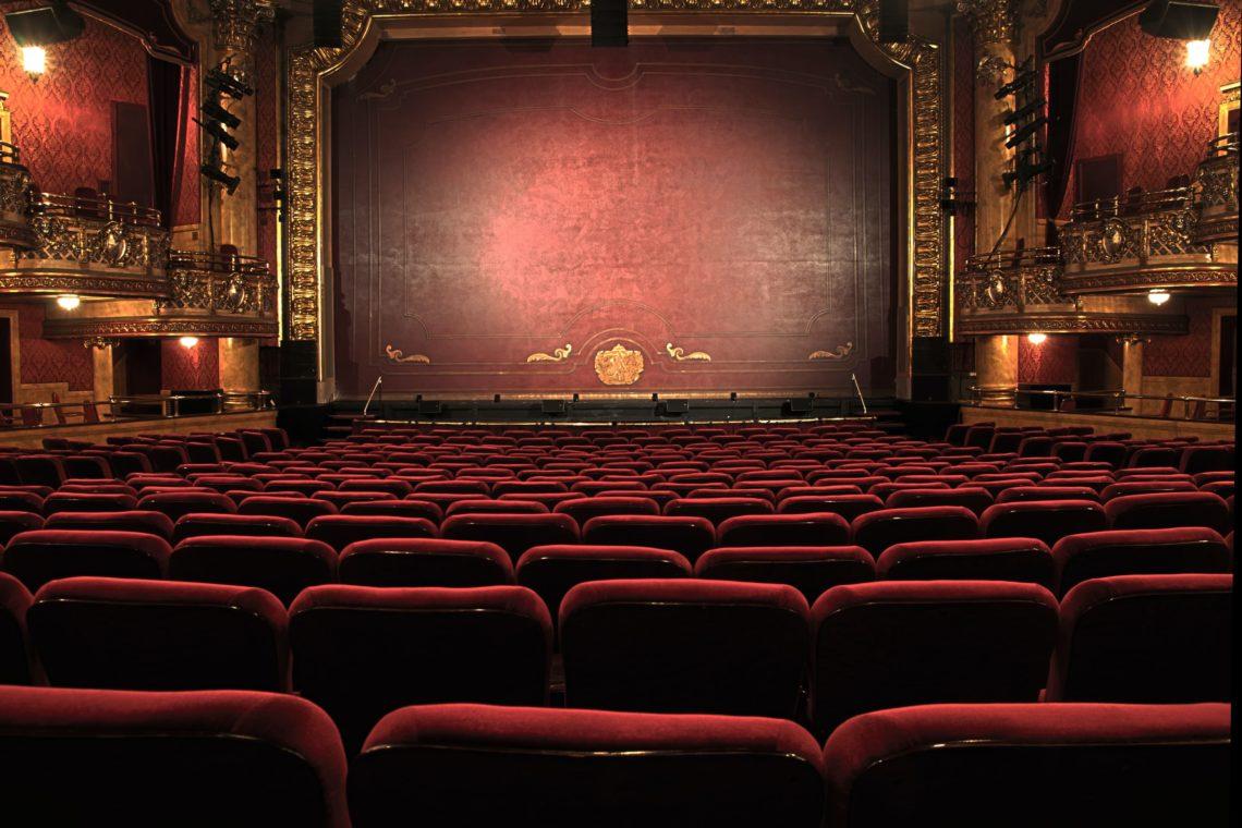 Φωτογραφία με θεατρικού χώρου με κέντρο τη σκηνή. Η αυλαία είναι κατεβασμένη και τα καθίσματα κόκκινα.Πηγή εικόνας: blog.redletterdays.co.uk