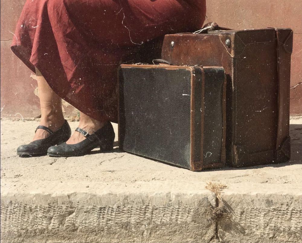 """Φωτογραφία εξωφύλλου για την μουσικοθεατρική παράσταση με τίτλο """"Το χρονικό των δέκα ημερώ"""". Στην φωτογραφία απεικονίζεται ένα κόκκινο βαθύ φόρεμα μίας καθιστής γυναίκας, από τη μέση και κάτω. Καθώς, στο πλάι της υπάρχουν δύο μεγάλες βαλίτσες παλαιού τύπου. Η φωτογραφία είναι ξεφθοριασμένη μίας άλλης εποχής."""