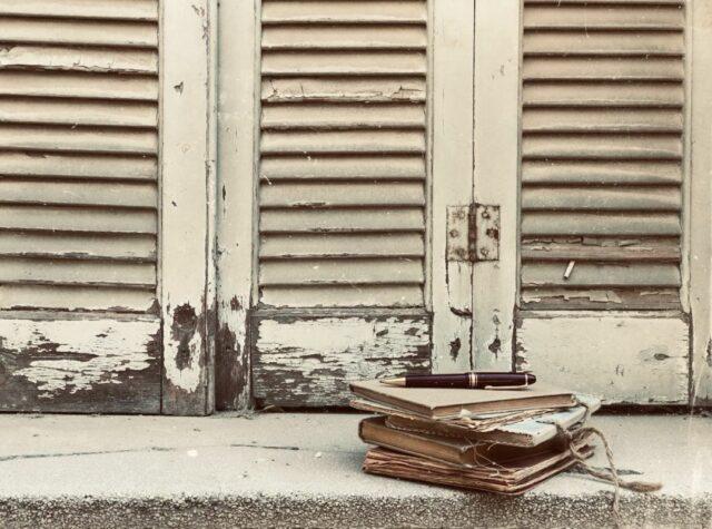 """Φωτογραφία για το δελτίο τύπου της παράστασης """"Το χρονικό των δέκα ημερών"""", η οποί απεικονίζει ένα παράθυρο με λευκά παραθυρόφυλλα παλαιού τύπου, ενώ στο περβάζι υπάρχουν παλιά σημειωματάρια"""