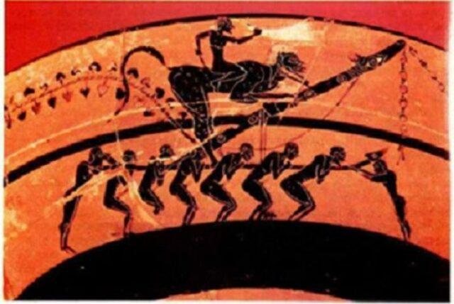 αττικό αγγείο του 560 π.Χ. Αναπαριστά .μια φαλλική πομπή, όπου οι πανηγυριστές κουβαλούν στους ώμους τους έναν υπερμεγέθη φαλλό. Αρχαία κωμωδία. πηγή: phalliphoria.gr